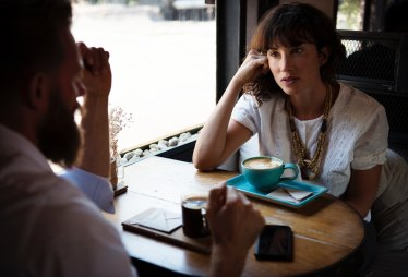 Two people talking in an uncomfortable conversation over coffee.