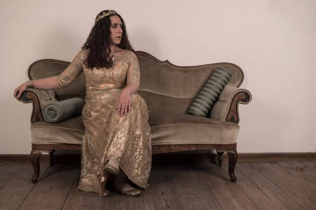 A woman dressed in gold with a crown sits on a sofa elegantly.