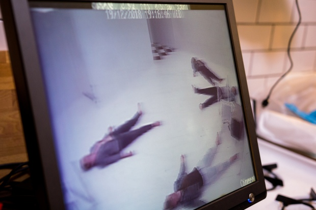 Dead bodies on a floor seen over a camera screen.