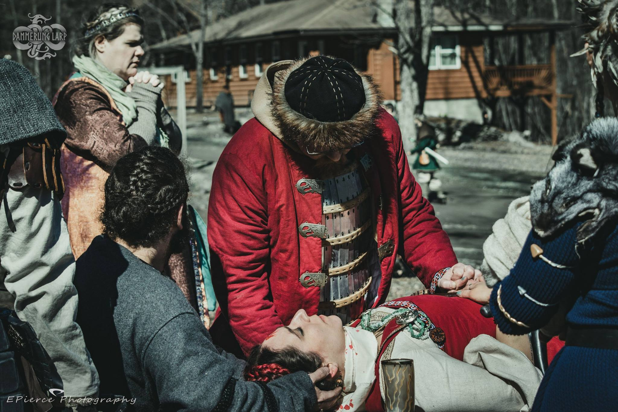 A man in viking clothing holds the hand of an unconscious, bloodied woman on a table as their religious adviser looks on.